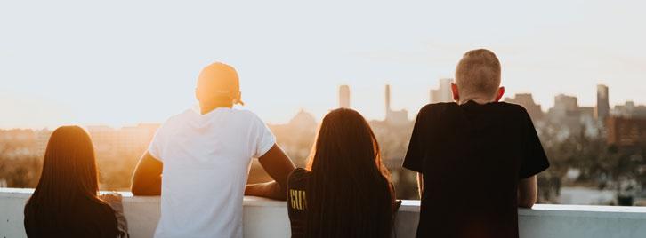 Vier Jugendliche schauen von einem Hochhaus auf die Stadt