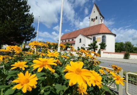 Kirche mit Blumen im Vordergrund